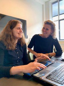 Foto van Willemijn en Angelique achter een laptop