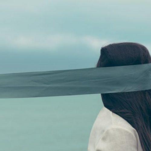 Vrouw met een blauwgrijs lint voor haar ogen